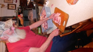 Hubby slices the meat off of the ham in slender strips to send through the grinder.