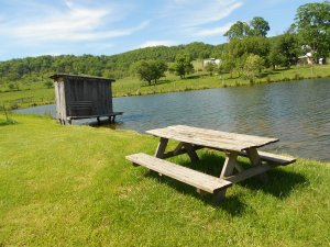 Picnic table and boat house full of fishing gear.