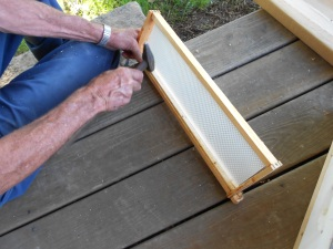 Tapping in the small strip that holds the comb straight.