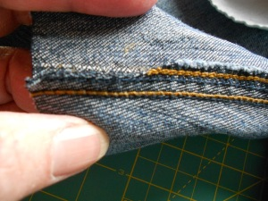 Next I trimmed the inseams to a thickness that would be easier on my sewing machine needle.  Denim folded several times will break a needle in quick order.