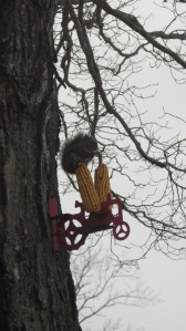 The squirrel feeder is a tractor with spikes coming up on both sides of the seat.
