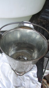 Gallon stainless steel bucket used to strain sap into tank.