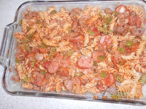 Meat mixture mixed up in casserole dish with cooked rotini and spaghetti sauce.