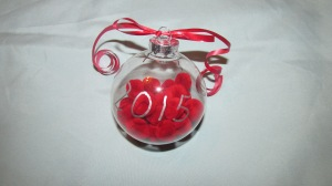 Clear ornament with mini red pompoms in the ornament and a ribbon tied on the hanger.