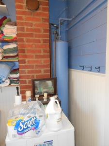 The blue tank beside the chimney is our water holding tank and the water circulates through the pipes of the woodstove in the kitchen.