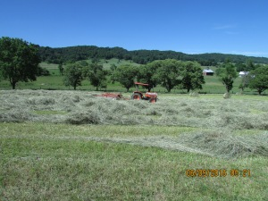 Kubota tractor and rake have completed their work in this field for today.