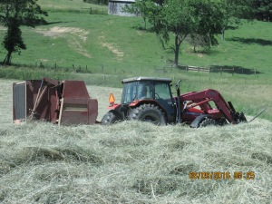 The 4x5 baler is hard at work as is the driver of the tractor that's pulling that baler.